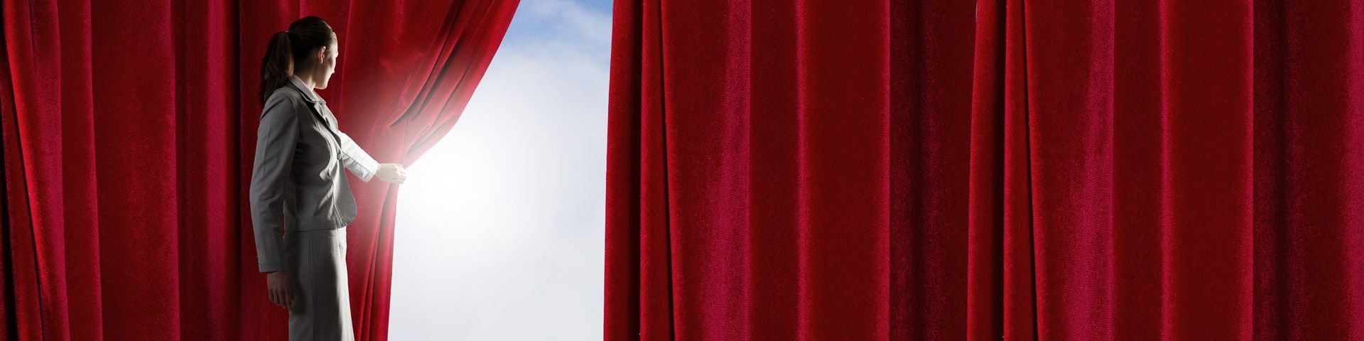 A woman wearing a business suit pulls back a red curtain to reveal a bright blue sky and clouds.